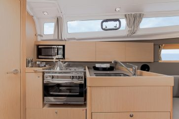 Beneteau 35.1 Interior kitchen view displaying all of the cooking appliances and storage.