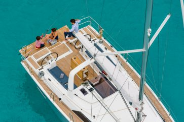 Beneteau 41.1 Family sitting on the stern swim platform enjoying the water.