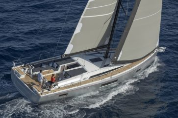 Beneteau 51.1 Under sail with with a couple manning the helm.