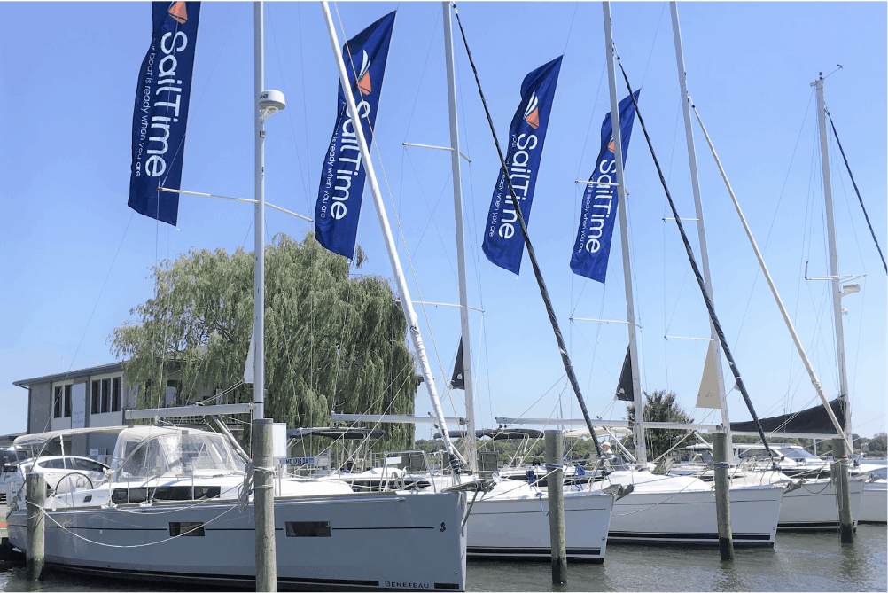 sailtime fleet of boats with jib banners in marina